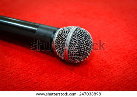 Microphone on red fabric background. speak speech audio karaoke song voice entertainment record object black. vintage style tone.