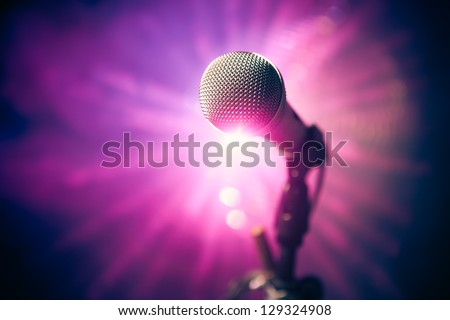 microphone on stage against purple rays - stock photo