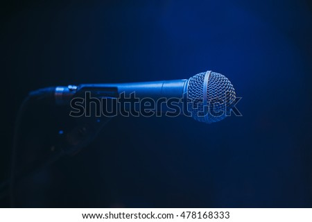 Microphone on stage on blue background.