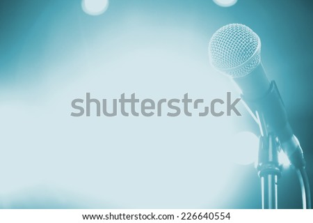 Microphone on stage with shiny rays as the background - stock photo