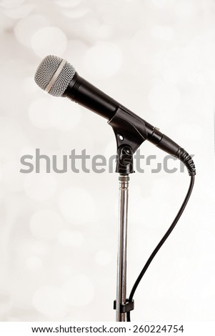 Microphone on stand on light background - stock photo