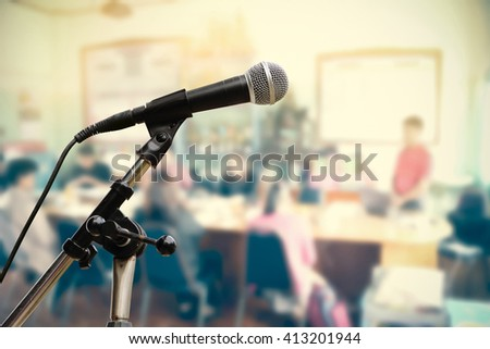 microphone on stand with blur people in seminar background - stock photo