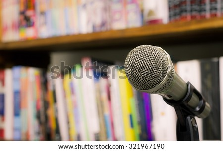 microphone on the background of blurred bookshelf  in library. soft focus .shallow depth of field. Vintage style and filtered process. - stock photo