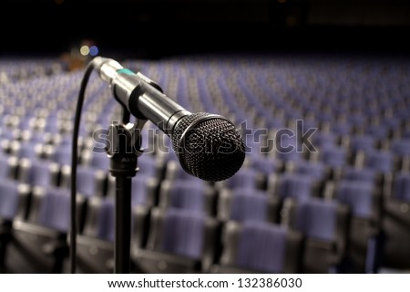 microphone on the stage and empty hall during the rehearsal - stock photo