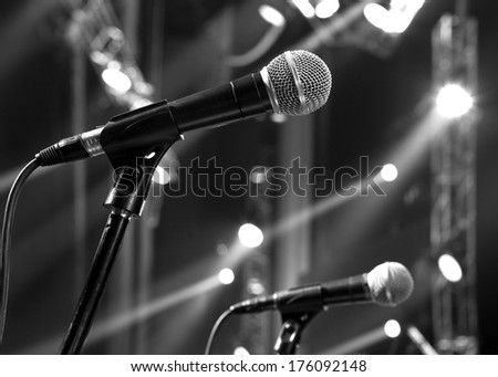 microphone on the stage and empty hall during the rehearsal black and white photo - stock photo