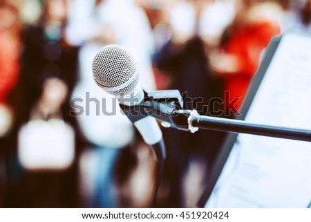 Microphone on the stand at the background of the crowd.