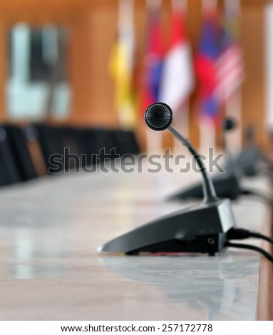 Microphone on the table in the conference room. - stock photo