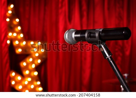 microphone on theater stage ,golden star on background  with red curtains  - stock photo