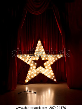 Microphone on theater stage,golden star  with red curtains around - stock photo