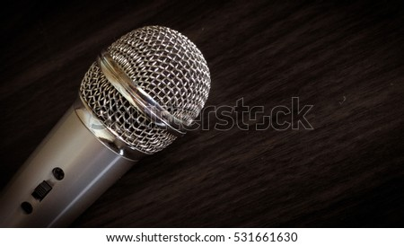 Microphone on wood brown background.
