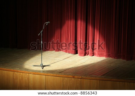 microphone on wooden stage, red curtain in background, spot light - stock photo
