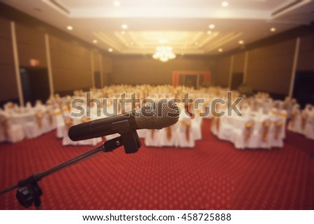 Microphone over the Abstract blurred conference hall or seminar room background or convention hall. - stock photo