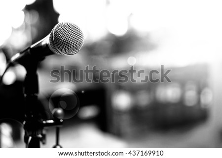 Microphone over the Abstract blurred photo of conference hall or seminar room background.