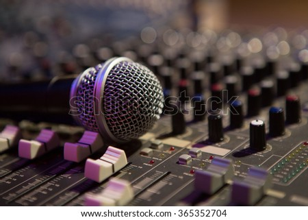 Microphone resting on a sound console in a recording studio - stock photo