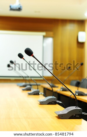 Microphone standing on a meeting room table - stock photo