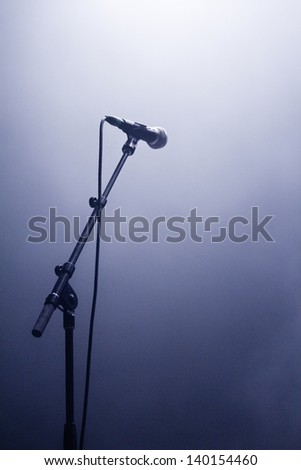 Microphone waiting for a voice in silhouette on a stage - stock photo