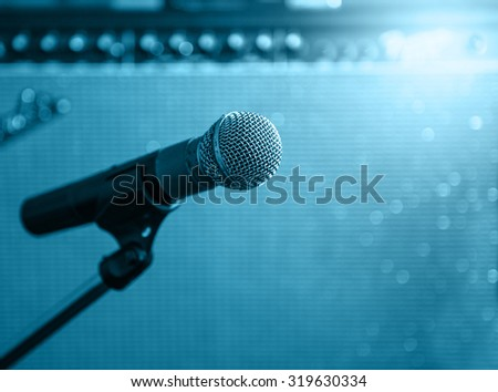 microphone with blurred Amp Speaker background ,blue tone style - stock photo