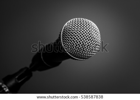Microphone with metal body in holder, isolated on black background, close-up