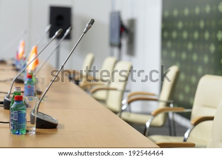 Microphones and drinking water on the table in the meeting room, nobody