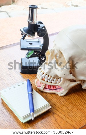 microscope and skull on wooden table