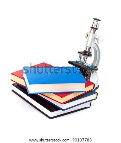 Microscope, books isolated on white - stock photo