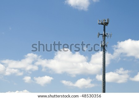 Microwave and cellular tower with partly cloudy blue sky