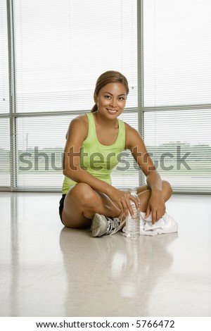Mid adult Asian woman sitting on floor with water bottle smiling at viewer.