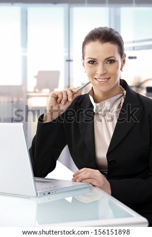 Mid-adult attractive businesswoman sitting at desk working with laptop computer, smiling. - stock photo