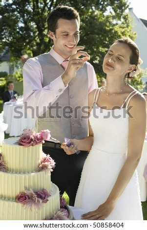 Mid adult bride and groom cutting wedding cake, groom putting bit of cake on bride's nose - stock photo