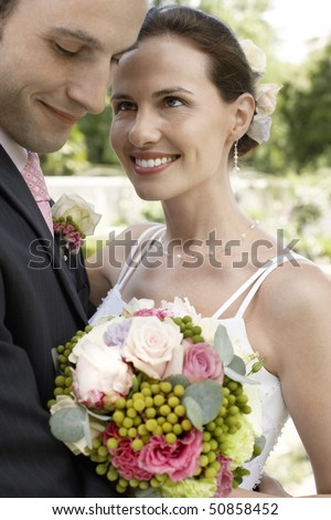 Mid adult bride and groom holding bouquet, smiling