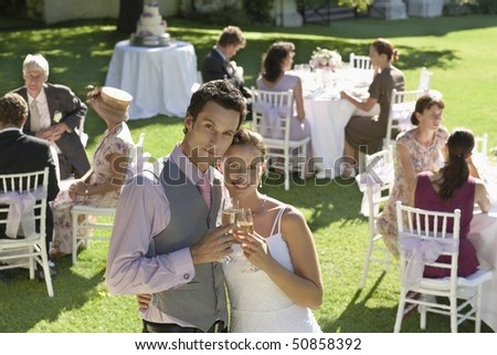 Mid adult bride and groom in garden among wedding guests, holding wineglasses, embracing - stock photo