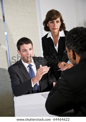 Mid-adult businessman and businesswoman meeting and negotiating with African American man - stock photo