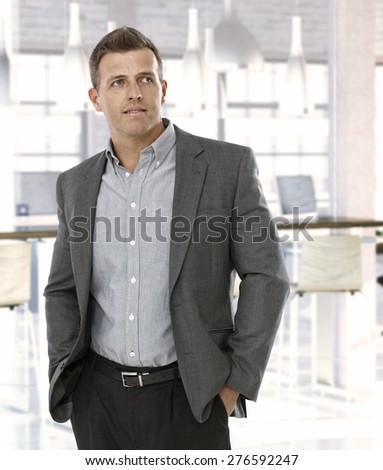 Mid-adult businessman at office, looking away.