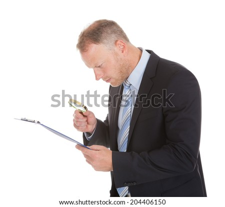 Mid adult businessman examining document on clipboard with magnifying glass over white background - stock photo