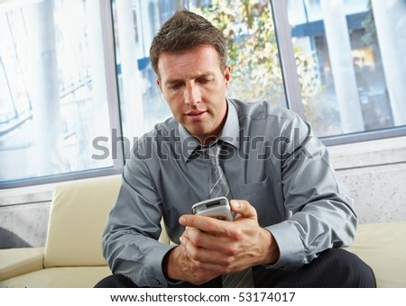 Mid-adult businessman looking down at mobile phone sitting on beige sofa in bright office. - stock photo
