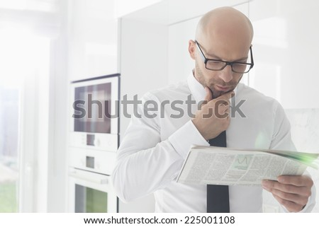Mid adult businessman reading newspaper at home - stock photo