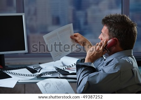 Mid-adult businessman talking on landline phone looking at business documents handheld in closeup. - stock photo