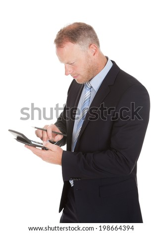 Mid adult businessman using calculator over white background - stock photo