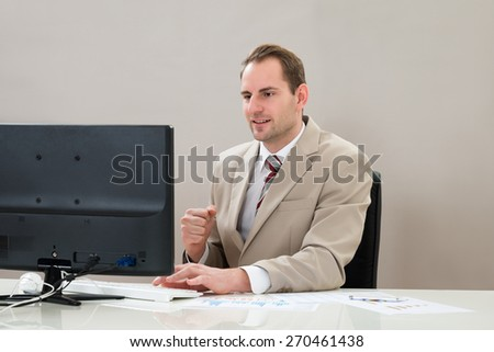 Mid Adult Businessman With Computer And Graphs At Workplace - stock photo