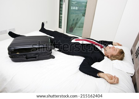 Mid adult businessman with luggage sleeping in bed at home - stock photo