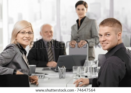 Mid-adult businesspeople sitting at meeting with colleagues in background, smiling at camera.?