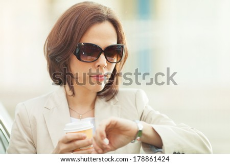Mid adult businesswoman checking the time on her wristwatch. - stock photo