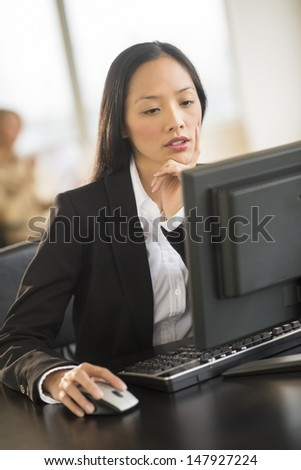 Mid adult businesswoman using computer at desk in office with female colleague sitting in background - stock photo