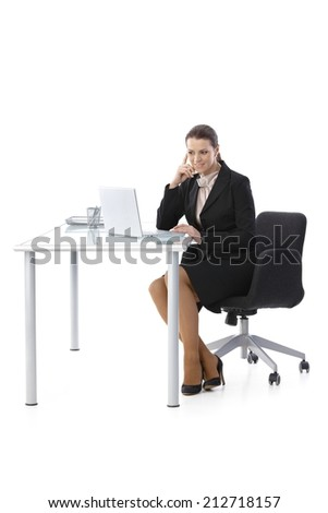 Mid-adult businesswoman working at desk, using laptop computer, smiling, cutout on white, full length.