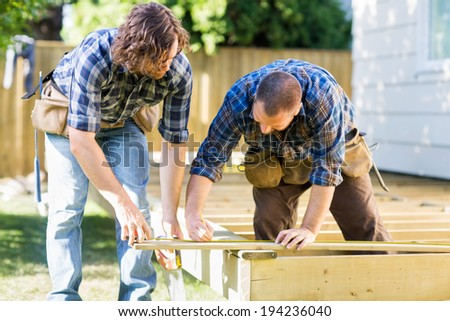 Mid adult carpenter marking wood while building deck - stock photo