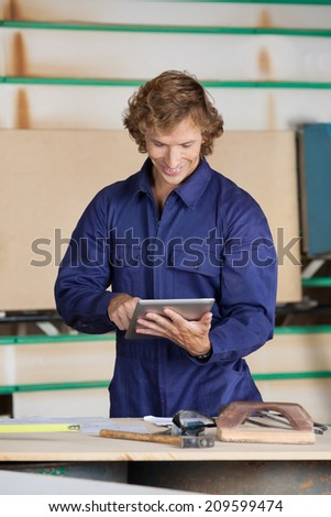 Mid adult carpenter using digital tablet at table in workshop
