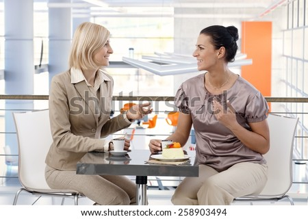 Mid-adult casual caucasian businesswomen talking about business at trendy cafe, sitting at table, having fun. - stock photo