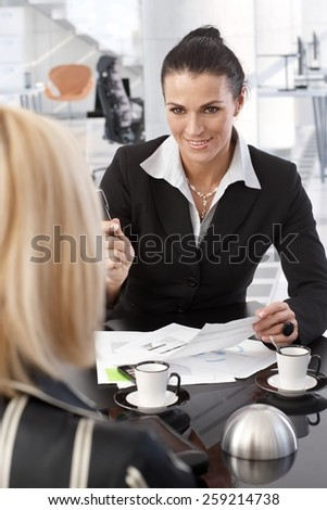 Mid adult caucasian brunette businesswoman signing contract over coffee at office table. Smiling, suit, pen in hand, focus in background. - stock photo