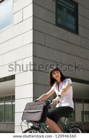 mid adult caucasian business woman commuting to office by bike and looking away - stock photo
