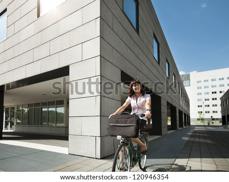 mid adult caucasian business woman commuting to office by bike and smiling - stock photo